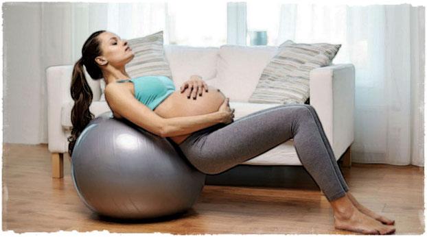 Беременная девушка лежит на фитболе