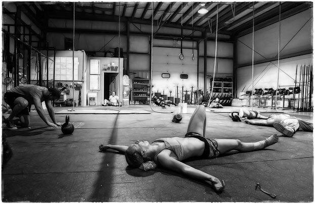 Девушка лежит на полу в спортзале усталость