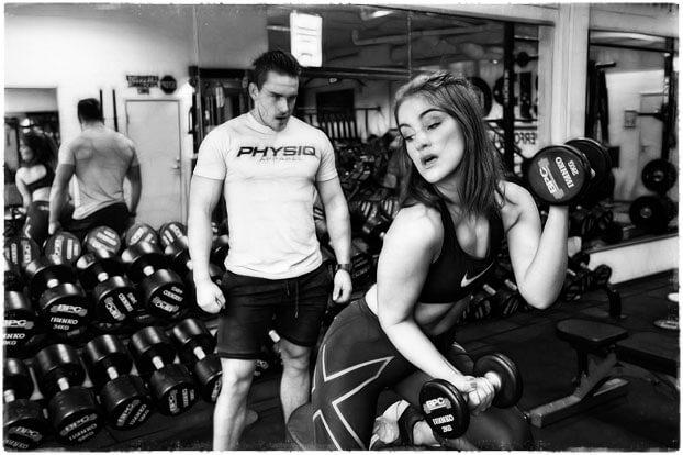 Парень смотрит на девушку в спортзале